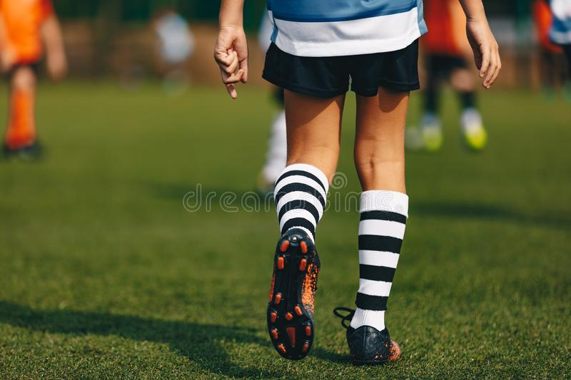 Legs of boy footballer in boots football cleats. Player walking on green grass soccer field at the stadium. Close-up of football sports equipment stock photo