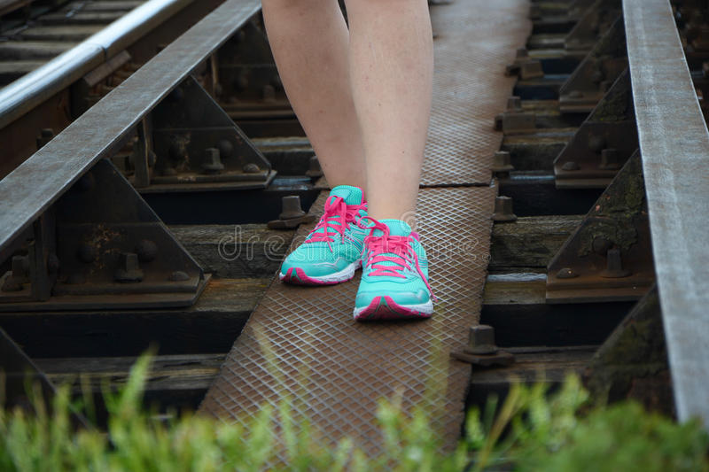 Legs in bright colorful sneakers walking on railway royalty free stock image