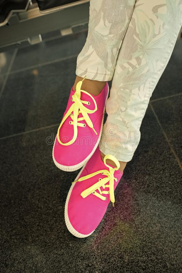 Legs in bright pink gumshoes. Legs or feet in bright pink gumshoes or canvas sneakers with yellow laces and stylish floral jeans on floor tiles on grey stock photography