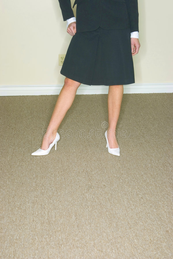 Legs-Business Woman. Business woman in suit with skirt, shown from waist down, legs and wearing white shoes stock photography