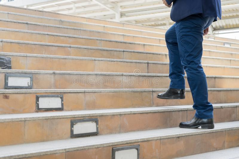 legs of businessman walking stepping up stair in modern city, bu royalty free stock photo