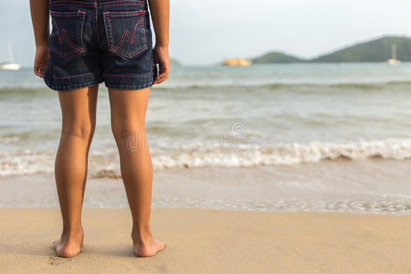 Legs of children stand on the beach royalty free stock photography