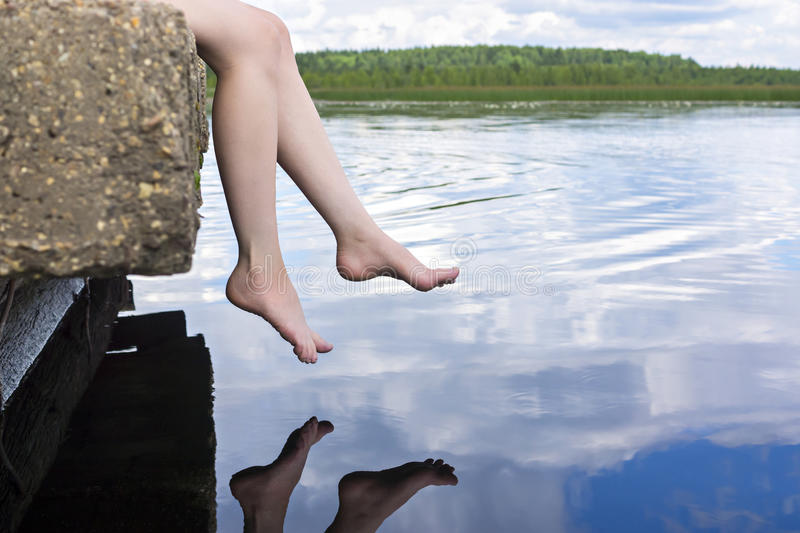 Legs dangling over water. Slender legs dangling over lake water relaxed stock photo