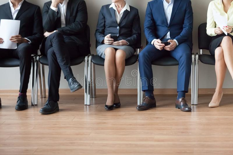 Legs of diverse work candidates waiting in turn for interview royalty free stock image
