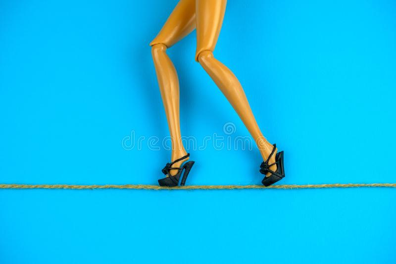 legs of a doll in black shoes walking on a tightrope on a blue background, strategy and business risks the concept royalty free stock photography