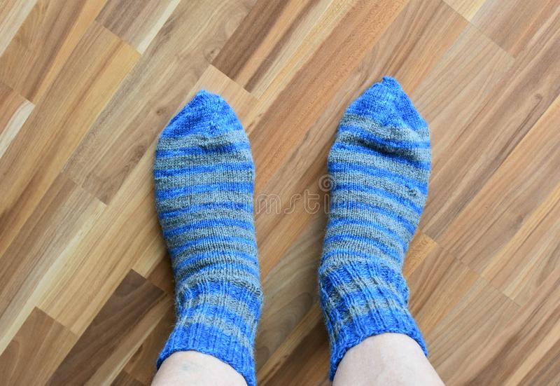 The legs of an elderly person in warm woolen socks. stock images