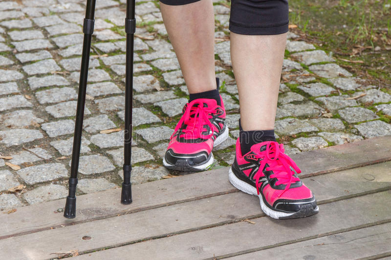 Legs of elderly senior woman and nordic walking sticks, sporty lifestyles. Legs of elderly senior woman in sporty shoes with nordic walking sticks, healthy stock image