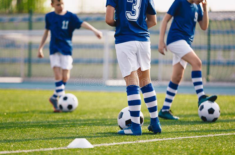 Legs of european football boys kicking balls on field. Group of young football players on soccer training. Football practice training background stock photos