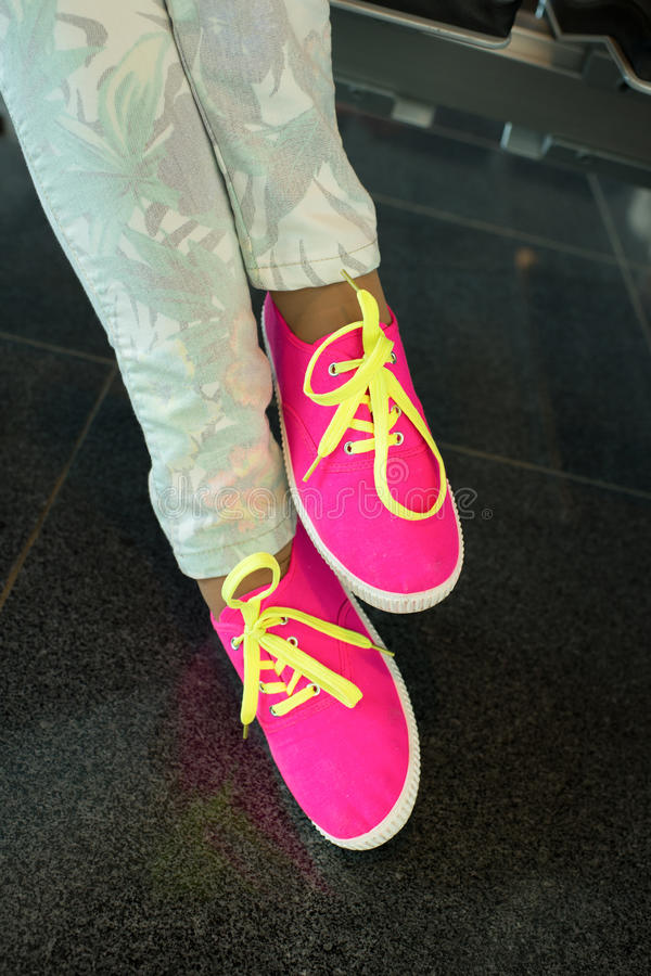 Legs in bright pink gumshoes. Legs or feet in bright pink gumshoes or canvas sneakers with yellow laces and stylish floral jeans on floor tiles on grey royalty free stock images