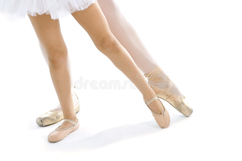 Legs and feet of classical Ballet dancer teacher and learning pupil training position stock image