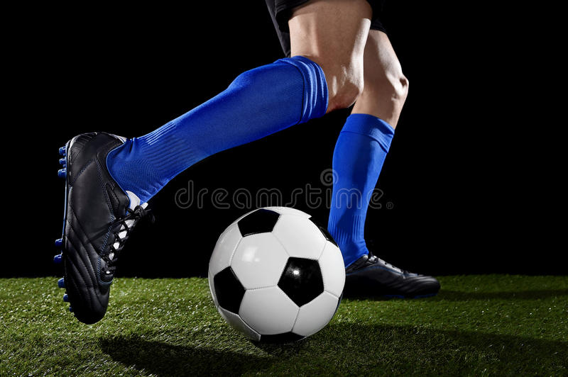 Legs and feet of football player in action running and dribbling with the ball playing on green grass royalty free stock photos
