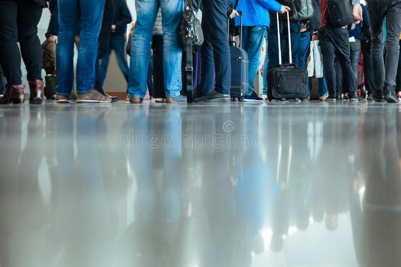 Legs feet stand landing gate bags baggage people airport terminal travel departure nether man many reflections floor stock photo