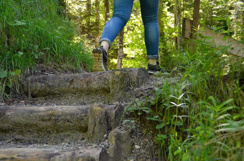 Hiking stairs legs and feet in forest. The legs and feet of a women hiking in a forest at stairs royalty free stock images