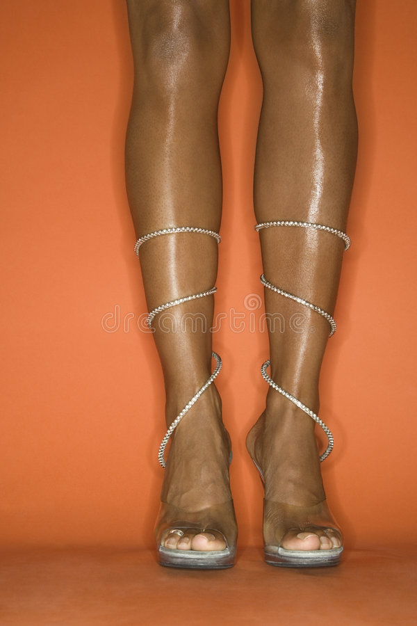 Legs and feet of young African-American woman wearing high heel stock photos