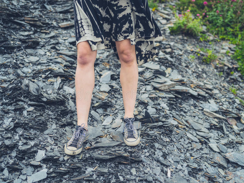 Legs and feet of young woman on rocks. The legs and feet of a young woman standing on some rocks outside stock photo