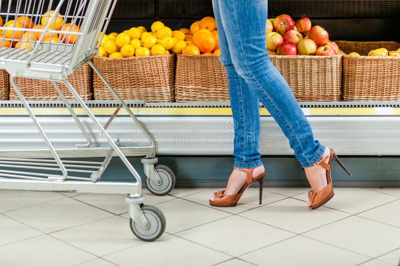 Legs of the female customer with cart stock photos