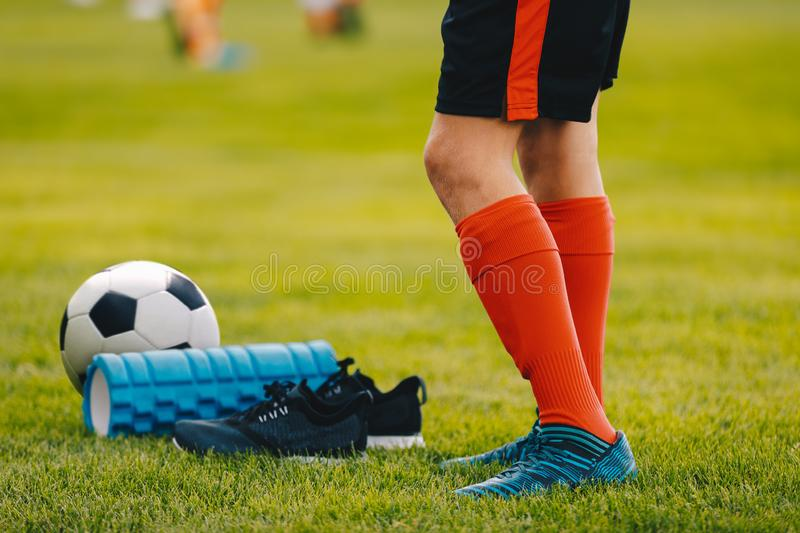 Legs of a football player boy in boots cleats with a ball and foam roller on the green lawn of the stadium. Football accessories equipment closeup royalty free stock photography