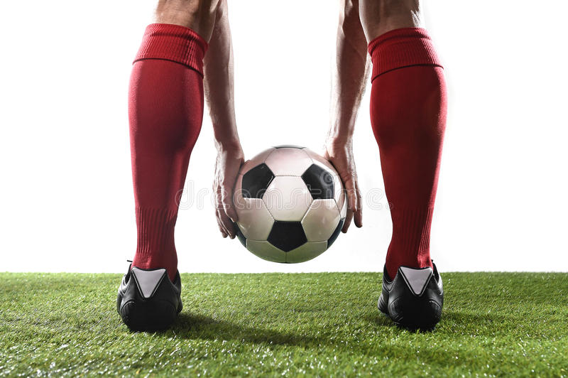 Legs of football player in red socks and black shoes holding the ball in his hands placing free kick stock photo