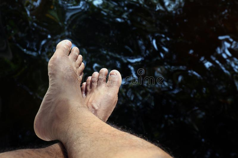 Legs and foots over the water surface stream for relax, travelers are sitting above the water for soaking their legs in the water stock images