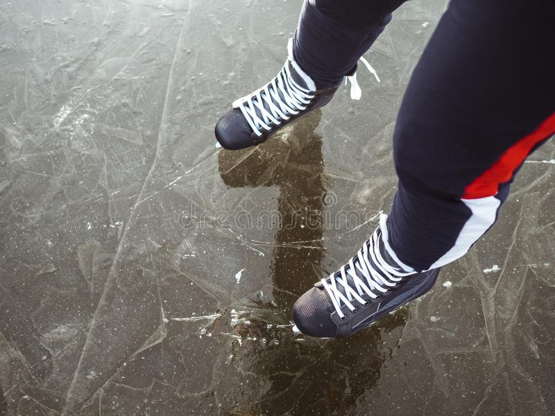 Legs of a girl in black hockey skates on ice. Photo above stock photos