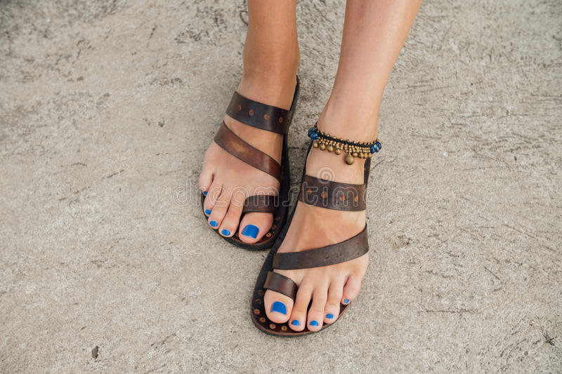 Legs of a girl with a blue pedicure in leather sandals on the pier royalty free stock image