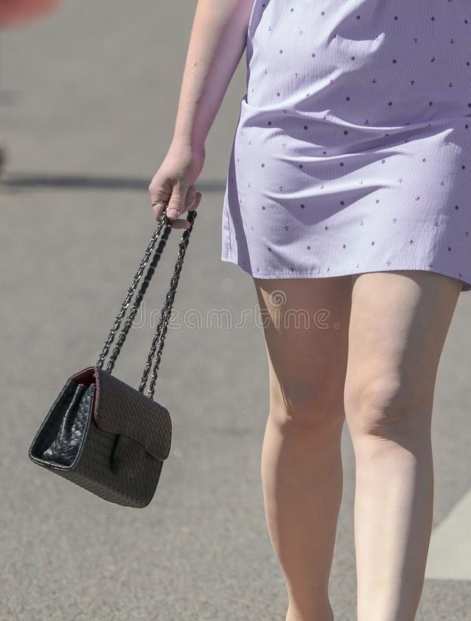Legs of a girl in a dress and a bag in her hand royalty free stock photo