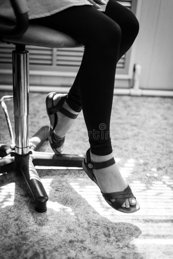 Legs of the girl in sandals sitting in a chair. black and white photo. girl in sandals stock image