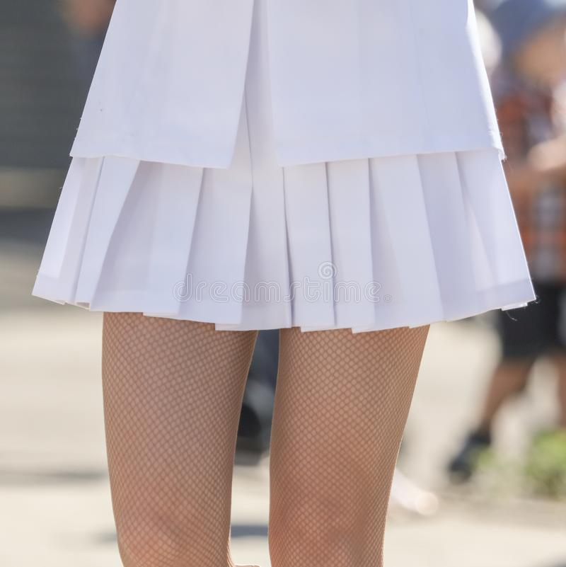 The legs of a girl in a short white skirt stock photos