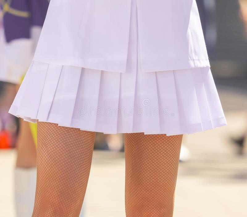 The legs of a girl in a short white skirt stock image
