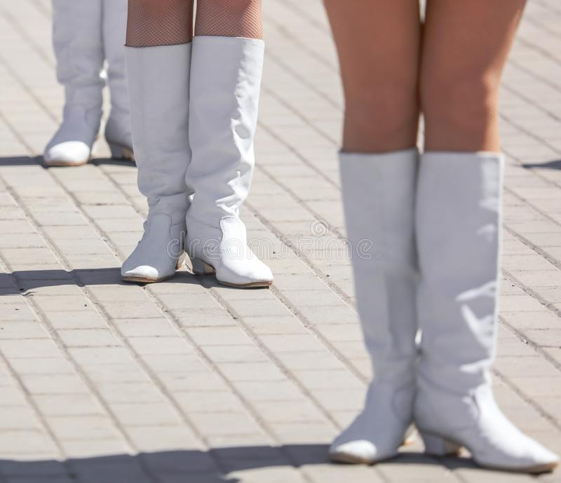 Legs of a girl in white leather boots royalty free stock photos