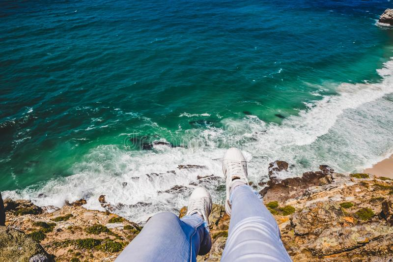 Legs hanging over the edge of a cliff stock photos