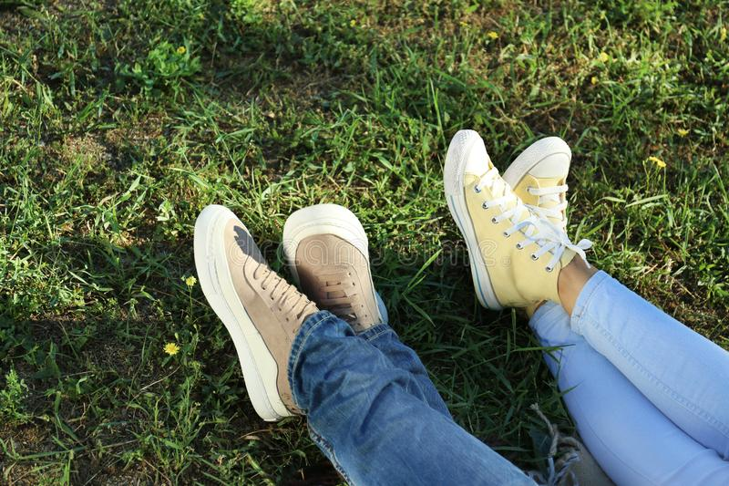 Legs of happy couple lying on grass in park stock photos