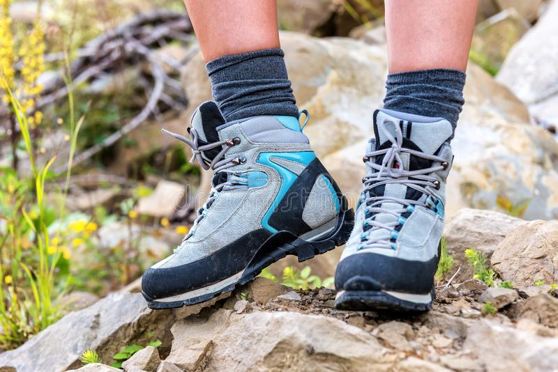 Legs in hiking boots. Legs in solid hiking boots on the rock royalty free stock image