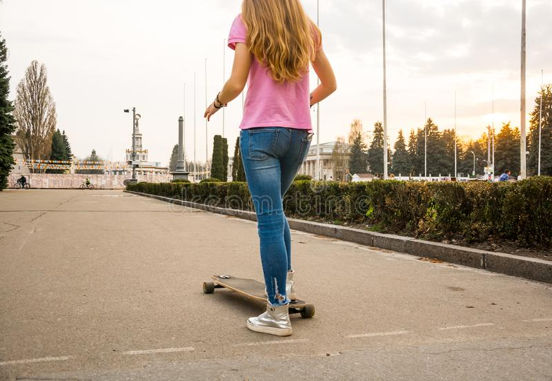 Legs of a hipster teenager-girl is riding a skateboard in a abandoned park in summer stock photos