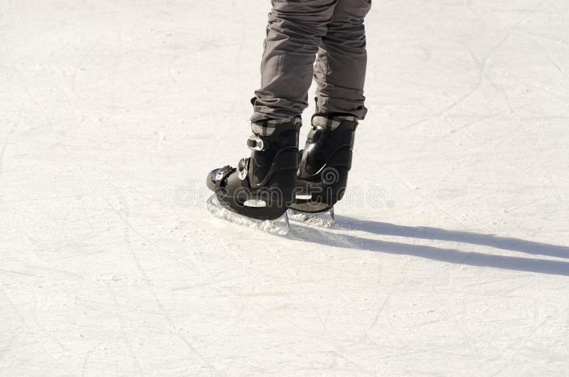 Legs of ice skater on ice rink royalty free stock image