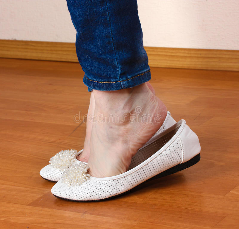Legs in jeans and ballet flat shoes stock images