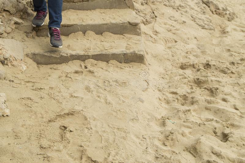 Legs in jeans and sneakers descending a stone staircase covered with sand, the concept of tourism, travel and exploration stock image