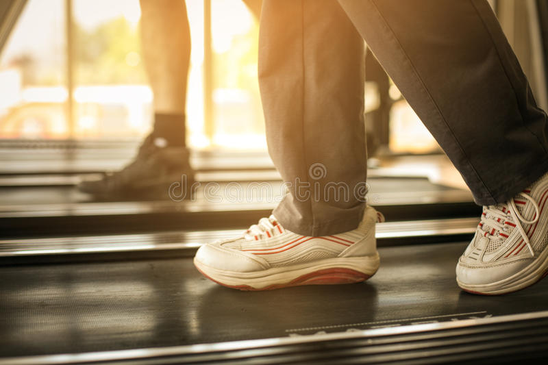 Legs in jogging machine. Senior couple workout in gym. stock images