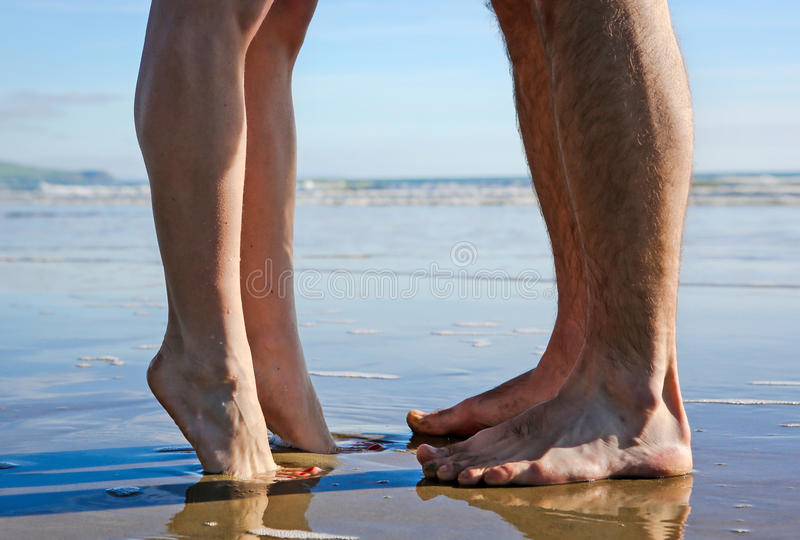 Legs of kissing couple on beach stock photography