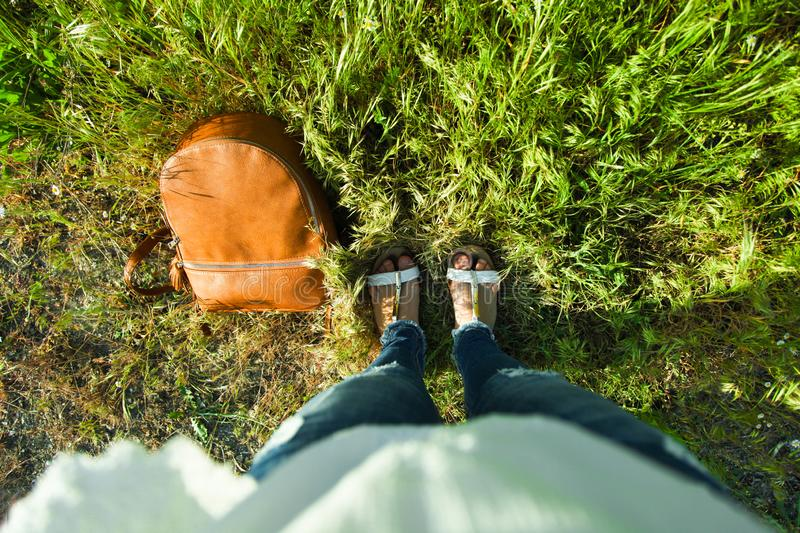 Legs and leather backpack. Girl`s legs and leather backpack in grass. Top view stock image