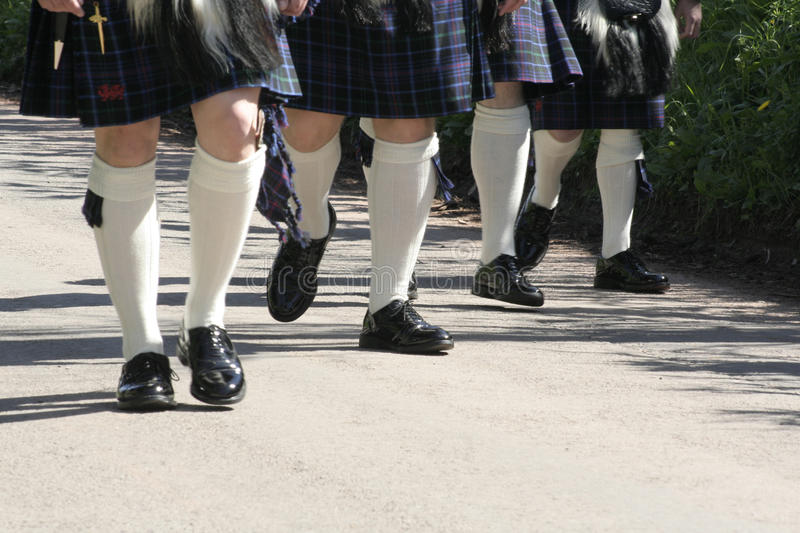 Legs in a line. Grooms party in kilts showing legs in white socks and highly poilished shoes royalty free stock photography