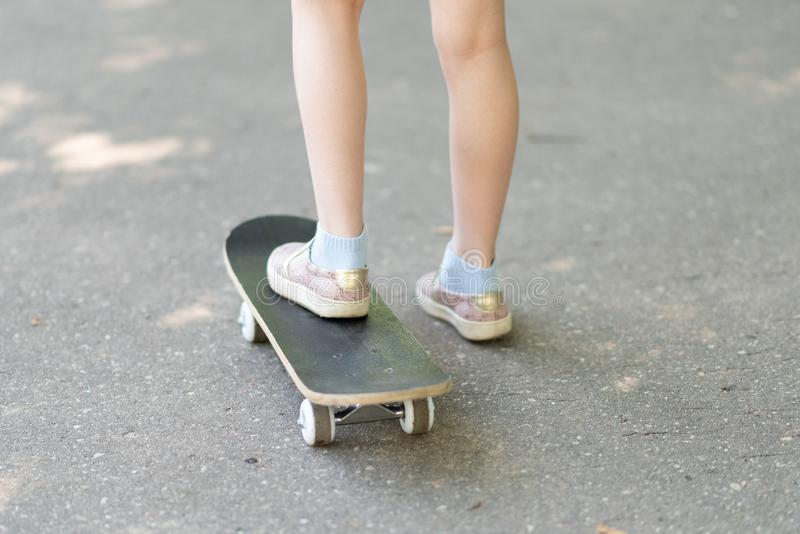 Legs of a little girl on a skateboard. For any purpose royalty free stock photography