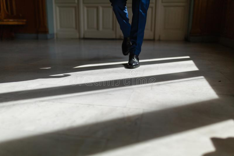 Legs of a man in an expensive suit and black shoes during a step. A person walks along the corridor of the living room or hotel ma stock photos