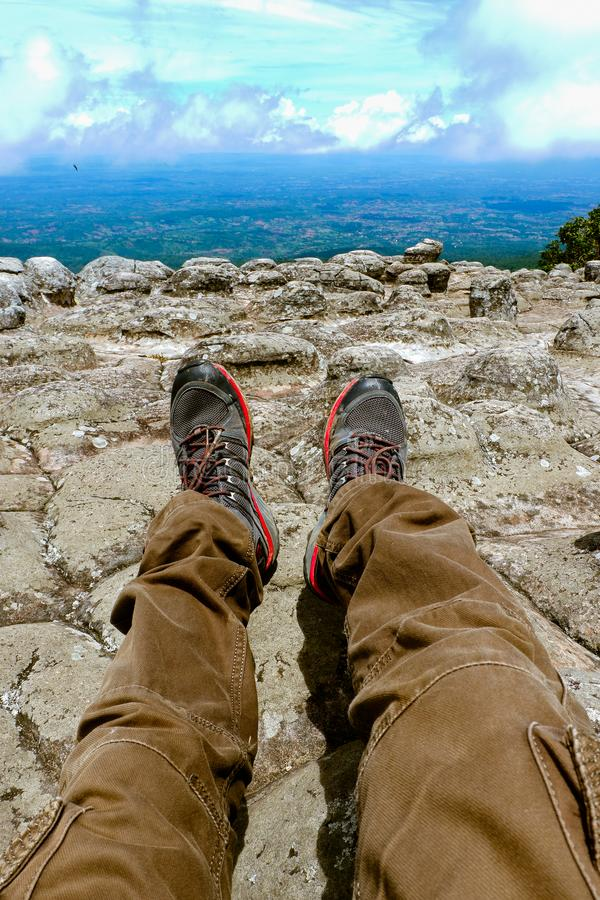 Legs of a man resting in boots for mountain tracking against the backdrop of mountains and valleys with noisy clouds Hiking boots stock image