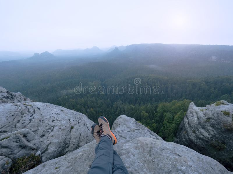 Legs of a man on rock. Hiker resting in boots for mountain royalty free stock images