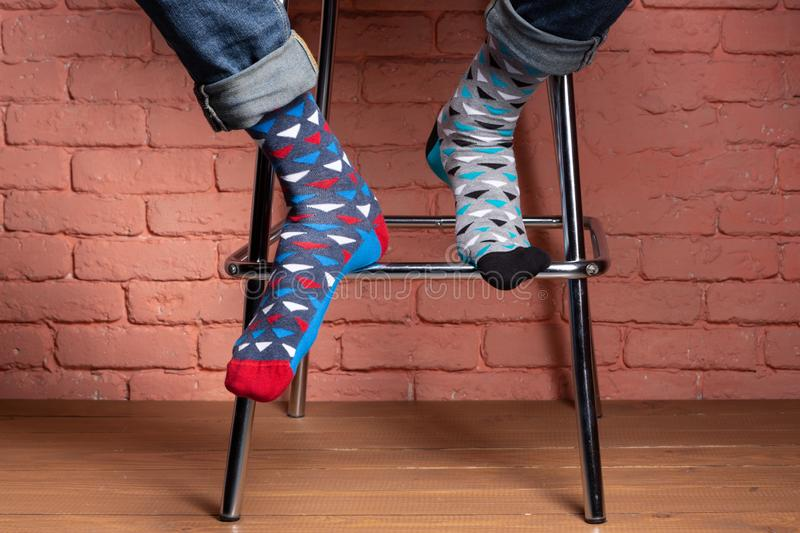 Legs of a man sitting on a high chair, in socks of different color, close-up, concept, against a brick wall royalty free stock images