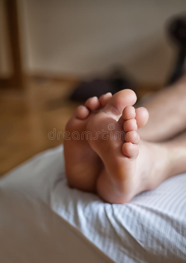 Legs of a man sleeping in bed. Legs with fingers of a man sleeping in bed royalty free stock photos