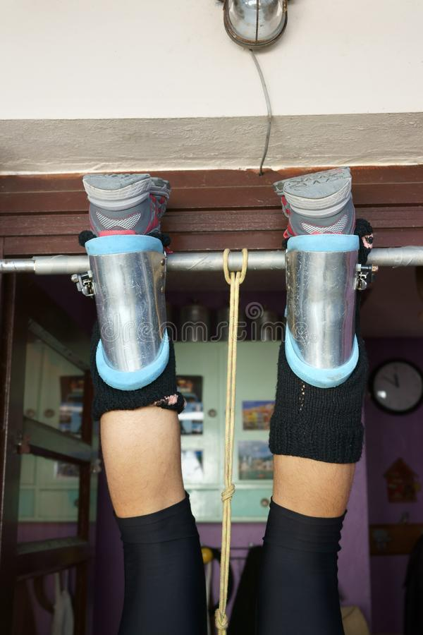 Gravity boots on hanging male legs Bar doorway royalty free stock photos