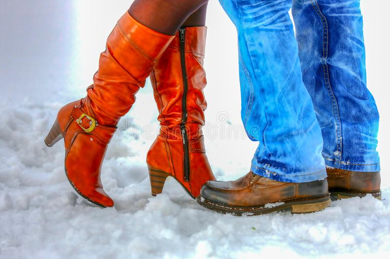 Legs Man and woman in winter boots standing in the snow. stock photo