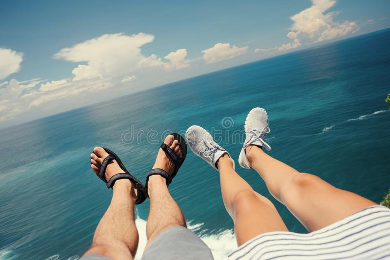 Legs of man in sandals and woman in sport shoes sitting above the ocean on cliff stock photo